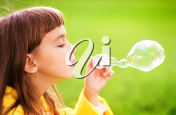 Portrait of cute girl blowing soap bubbles