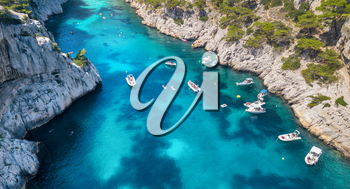 Yachts at the sea in France. Aerial view of luxury floating boat on transparent turquoise water at sunny day. Summer seascape from air. Top view from drone. Seascape with motorboat in bay. Travel concept and idea