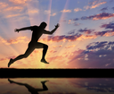 Running sports. Runner athlete and his reflection in the water on the sunset background