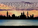 Concept of a border zone. Silhouette of the city behind a fence with barbed wire on a background of sunset and sea