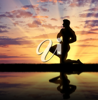 Concept of beauty and sports. Silhouette of bodybuilder posing at sunset and its reflection in water