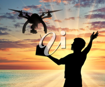 Silhouette of a flying drone, and a man with a remote control on a background of sea sunset. Concept quadrocopters