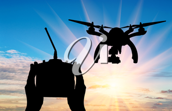 Silhouette flying drones and hands with remote control outdoors. Concept quadrocopters