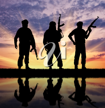 Silhouette of three terrorists with weapons at sunset with reflection in water