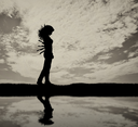 Betrayal and treachery concept. Silhouette of a sad woman with a knives in back and reflected in water