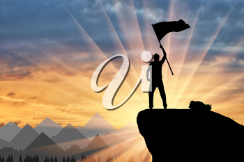 Silhouette of a climber on a mountain top with a flag in his hand. ?oncept of power and success