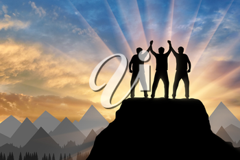 Silhouette of happy three climbers on the top of the mountain holding hands. Concept of teamwork