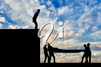 Silhouette of the man intends to make a leap down, people vnitsu help him safely land. The concept of mutual assistance of people