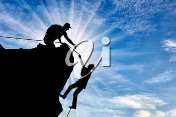 Silhouette of a climber who helps to climb the top of a man, throws him a rope and holds out his hand. Conceptual help scene