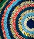 An image depicting a colourful crochet granny blanket.