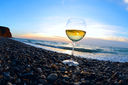 Romantic glass of wine sitting on the beach at sunset