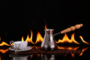 Turk and cup on coffee beans on a background of fire, black background. CONCEPT vivacity and energy