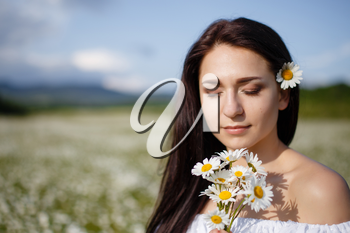 Beautiful woman on a flower granden enjoying her time outdoors. pretty girl relaxing outdoor, having fun, holding plant, happy young lady and spring green nature, harmony concept