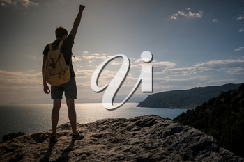 Hiker with backpack standing on top of a mountain with raised hands and enjoying view