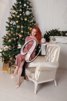 fashion interior photo of beautiful sensual woman with red hair in luxurious dress posing beside a Christmas tree