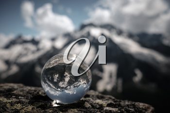 Transparent glass sphere and snow-capped peaks in the background. Concept and idea of travel