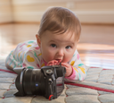 Young caucasian baby girl lying on carpet or rug and playing with an expensive camera as a budding photographer