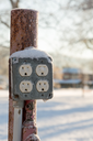 Snow covered electricity sockets or outlets that would not meet current building code requirements with snow filling the electrical connections