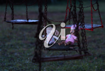 Halloween image of an abandoned childs dolly and small soft toy of girl on old rusty swing at fun fair