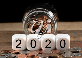 Cash in savings jar for good luck as dice for 2020 is spread on table for New Years celebrations