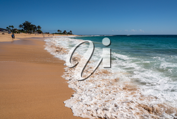 Holidaymakers on the sand of Sandy Beach on the east coast of Oahu in Hawaii in winter