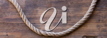 wooden board with a rough texture and a rope with a knot. Blank space for text