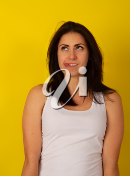 Pretty girl with dark hair in casual clothes in good mood makes a wry face and makes a face on a bright yellow background