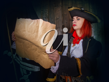 Young attractive armed girl pirate captain considers map against flag background Jolly Roger