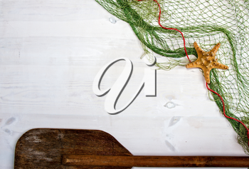 old white wooden boards on top of which lies a fishing net with starfish and an oar. With place for your text.