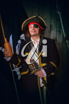 Adult pirate captain in a traditional costume and with weapons drinks rum from a clay bottle against the background of a jolly roger