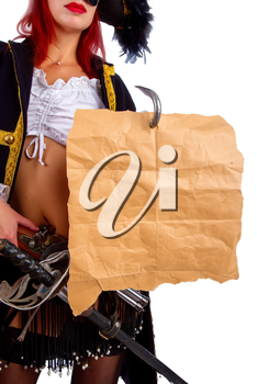 sexy girl in a pirate costume and a cocked hat stands on a white background holding a piece of old parchment worn on a hook with an empty place for text or card.