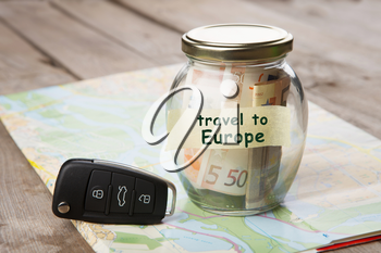 Travel by car to Europe - money jar, car key and roadmap