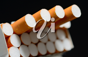 Closeup shot of white pack of cigarettes on a black background.