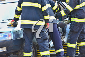 Firefighters and doctors helping the driver after car accident.