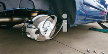Close-up of a car disc brake with caliper during tyre replacement. Car maintenance.