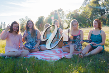 Young Girls Sitting Together in Grassy Field Singing and Playing Musical Instruments With Sunlight Overhead