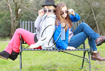 Two Girls Sitting on a Bench with Sunglasses