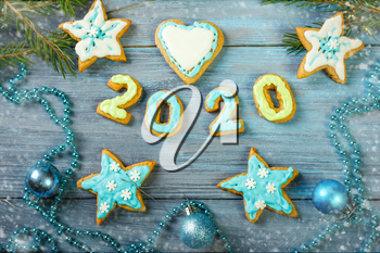 Glazed Christmas gingerbread and Christmas tree branches on a blue wooden background