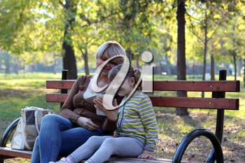 mother and daughter sitting in park and play with tablet