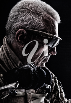 Close up studio shot of special forces white-haired veteran with knife. Sudden death killing concept