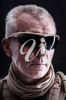Close up studio shot of special forces white-haired veteran in field uniforms, black background. Protective goggles glasses are on