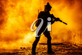 Black silhouettes of soldier in the smoke fire burning moving in battle operation. Back light
