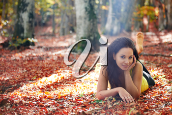 Pretty girl in the autumn forest laying on yellow leaves