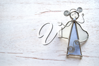 Angel figurine of the glass and wire isolated on wooden background. Abstraction