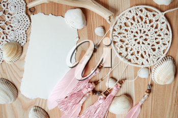 Seashells frame on wooden background with place for text. Card for a beach party, invitation, advertising. Dreamcatcher with pink feathers