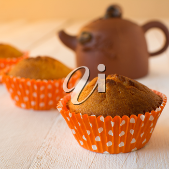 Muffins in orange paper cupcake holder with white polka dots and brown ceramic teapot on a white wooden background, selective focus, square