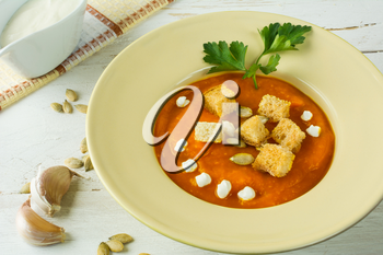 Pumpkin squash vegetable soup with cream, pumpkin seeds, garlic croutons and parsley in a light yellow plate on white wooden background, close up