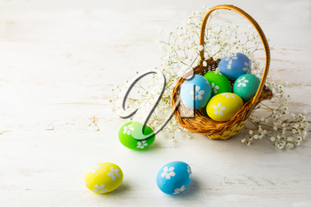 Decorated Easter eggs in the basket with small white baby's breath flowers on a white wooden background, space for text, copy space