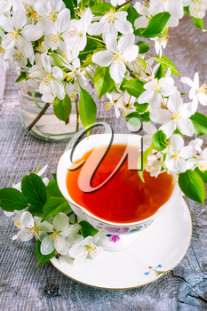Cup of tea on wooden table and apple blossom. Tea time concept. Breakfast tea cup served with flowers.