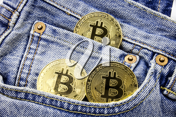 Three golden bitcoin coins on the pockets of the jeans. Concept of making money with online business. Making money motivational message. Online making money with bitcoin.